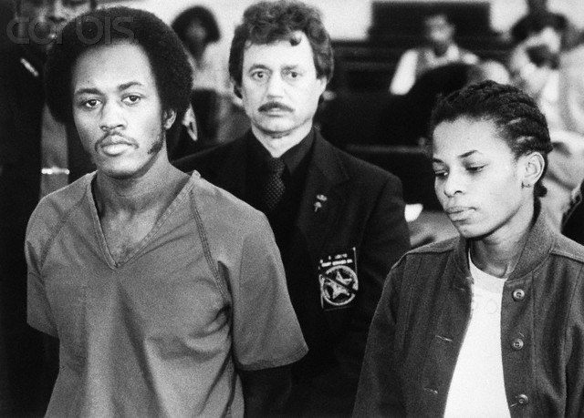 09 Jan 1985, Cincinnati, Ohio, USA --- Original caption: Fugitives Alton Coleman and Debra Brown express little emotion as they are arraigned 1/9 on a series of charges, including two counts of aggravated murder, as an unidentified sheriff's deputy stands guard. Coleman and Brown allegedly went on a six-state crime spree last summer and were captured in the Chicago suburb of Evanston, Illinois. --- Image by © Bettmann/CORBIS