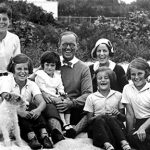 """PC 8 The Kennedy Family at Hyannis Port, 1931. L-R: Robert Kennedy, John F. Kennedy, Eunice Kennedy, Jean Kennedy (on lap of) Joseph P. Kennedy Sr., Rose Fitzgerald Kennedy (behind) Patricia Kennedy, Kathleen Kennedy, Joseph P. Kennedy Jr. (behind) Rosemary Kennedy. Dog in foreground is """"Buddy"""". Photograph by Richard Sears in the John F. Kennedy Presidential Library and Museum, Boston."""